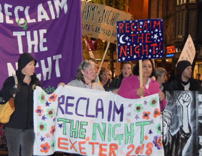 Protest march lead by banner reading Reclaim The Night